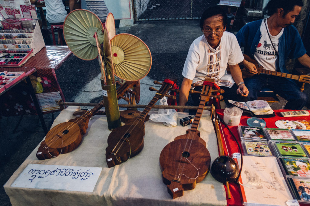 Man selling his musical instruments on a market in Lampang