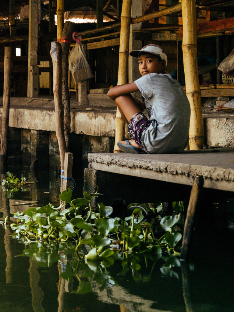 Child sitting along the klongs
