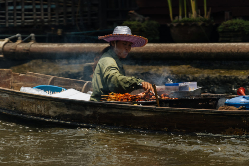 Woman cooking street food on a boat on the Klongs of Bangkok