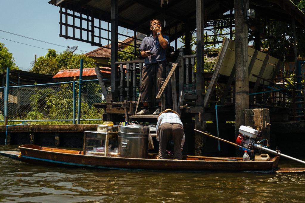 Man buying some food from a boat, Klongs, Bangkok