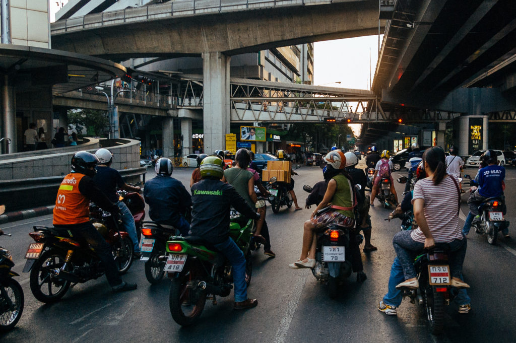 People on motorbikes waiting at a traffic light in Bangkok