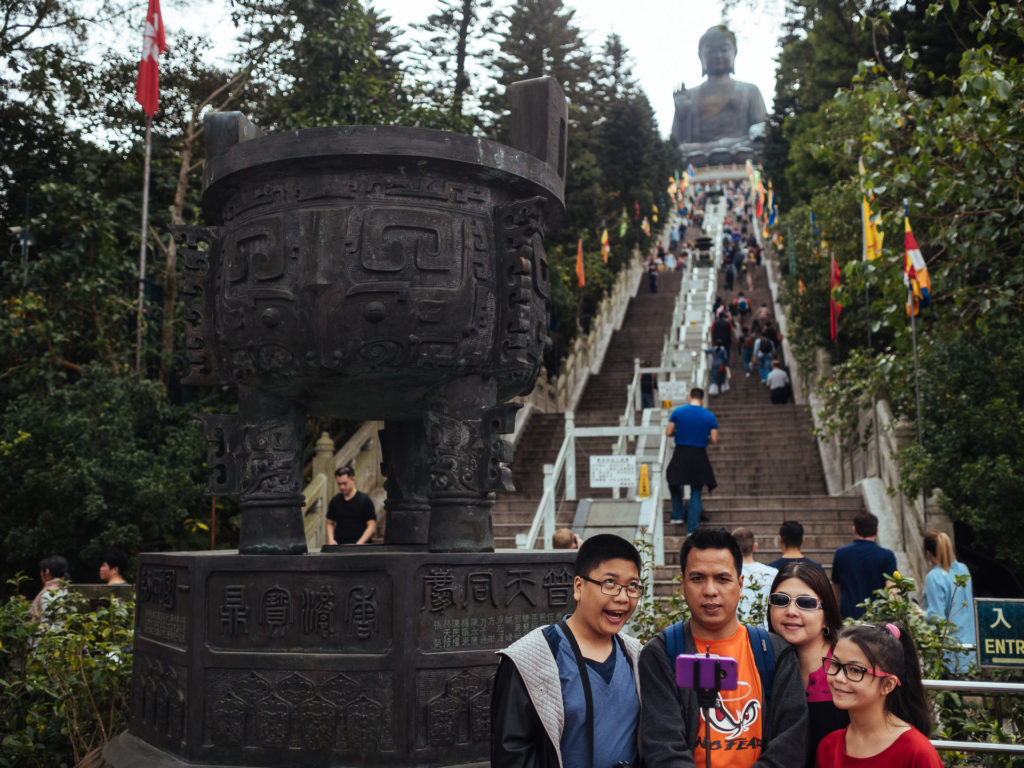 Tourists posing for a selfie with Buddha in the background, Po L