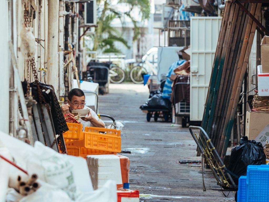 Une ruelle de Sai Kung avec un monsieur qui mange des nouilles