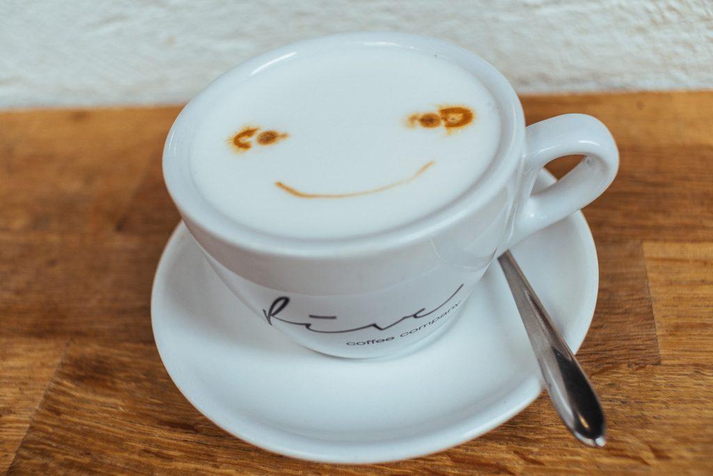 Capuccino avec un sourire dans la mousse servi chez Five Coffee Company à Sai Kung